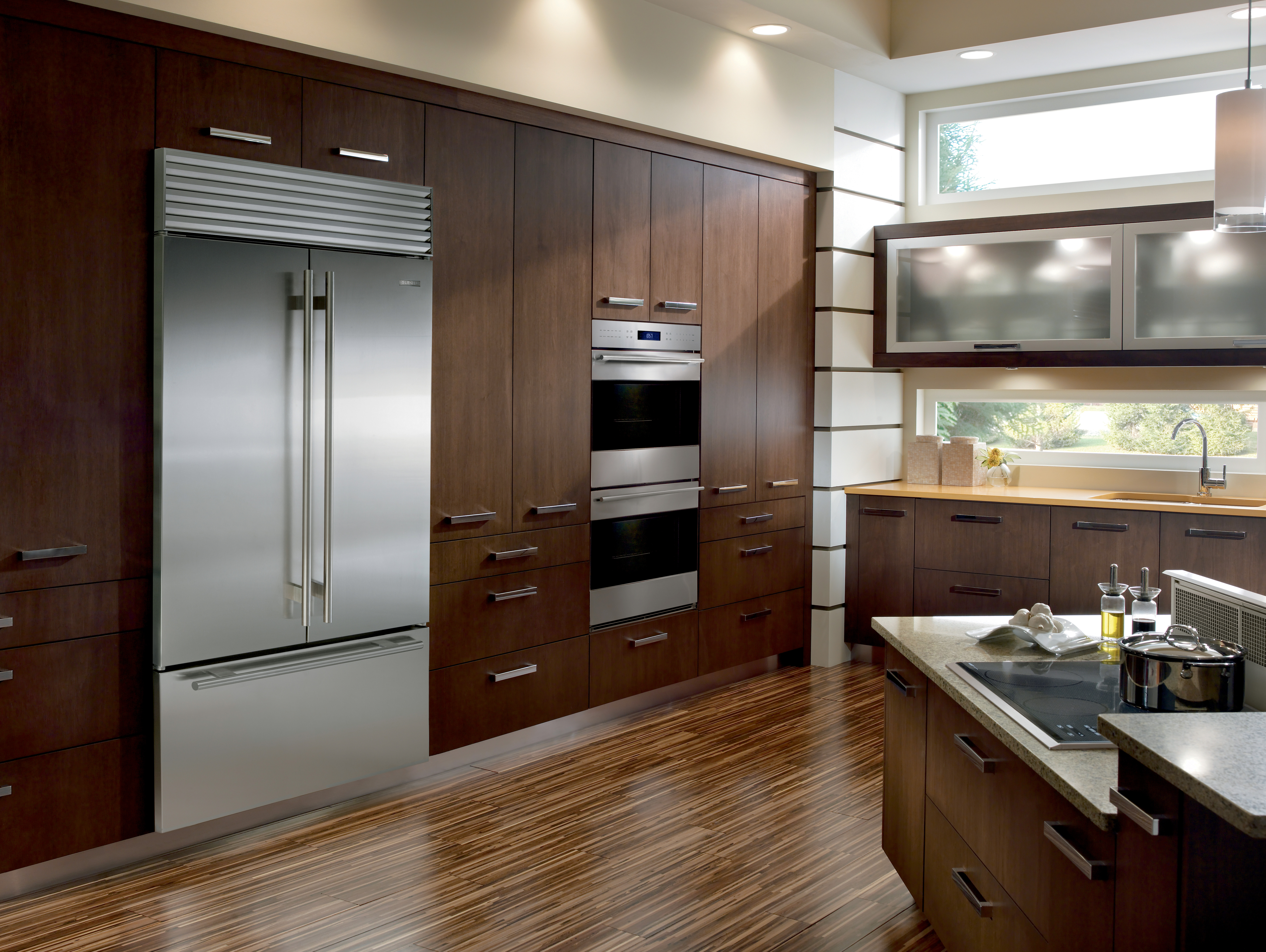 Sub-Zero BI-42UFD/S/TH all stainless in kitchen with dark brown cabinets and hardwood flooring.